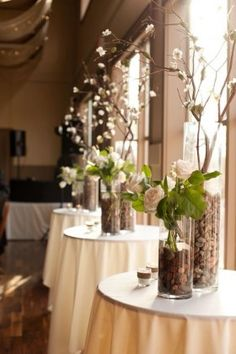 Cylinders with river rock roses and branches wedding centerpiece