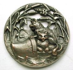 """Old French Metal Button Pierced w/ 2 Kittens Floating in a Wooden Shoe 1 & 3/16""""   Wonderful old French metal button. Lovely image of 2 kittens floating in a wooden shoe in a marshy area. Wonderful detail. Very good condition.  Measures 1 & 3/16 inch  SOLD $51.00"""