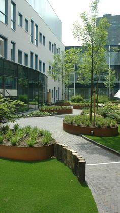 Centro empresarial o de oficinas con una zona verde de diseño que incluye #cespedartificial