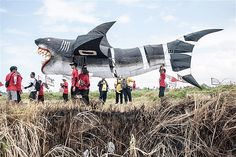 Participants prepare to fly a shark-shaped kite during the Bali Kite Festival in Denpasar, Indonesia, on July 26