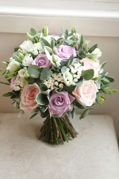 Wedding bouquet of ocean song and sweet avalanche roses, bouvardia, eustoma, freesia and foliage.