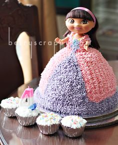 Dora Doll Cake ~ C HATED the mermaid doll when we were in the store so I found a more durable, less intimidating, less expensive bath time Dora (complete with a Boots water squirter lol) but I can. not. wait. to make this cake for her birthday!!  Cupcakes for all the guests too :)