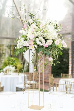 large wedding reception arrangement of white hydrangea, white o'hara rose, sweet akito rose, white stock, spirea, white majolik spray rose, light pink ranunculus, light pink parrot tulip, & greenery on tall modern gold pedestal under a clear tent.