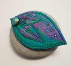 Leaf shaped brooch made with sumptuous hand dyed merino fibre in beautiful shades of teal and cerise. Iridescent beads add a little detail and a sturdy brooch bar is hand stitched on the back. Great for keeping cardigans and shrugs closed at the front or for use on a shawl, lapel, hat or bag.  Brooch measures 8cm long and 5cm wide.  Comes on an Aileen Clarke Crafts display card with cellophane sleeve for protection.  Handmade in Scotland.  © Aileen Clarke