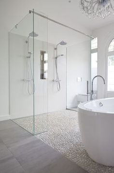 Shower floor - Modern bathroom features a crystal chandelier free standing acrylic tub a mix of marble tile and pebble floor and a double shower with custom made glass panels. Wet Rooms, Dream Bathrooms, Beautiful Bathrooms, Modern Bathrooms, White Bathrooms, Luxury Bathrooms, Bathrooms Suites, Tiled Bathrooms, Modern White Bathroom