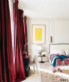 L'Wren Scott's Paris bedroom with patterned bedspread and red curtains.
