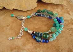 blended, deep ocean, blue and green tones into this rich layered beadwork bracelet. Included in this necklace are, Turquoise, Amazonite, Aventurine, Green and blue Agate, Fire Crackle Agate, vintage pressed glass beads, Labradorite (natural) and a large vintage lampwork glass bead. I used tribal style silver throughout and finished this bracelet with an oversized lobster clasp, beaded extension chain and Sea Turtle charm, by BohoStyleMe