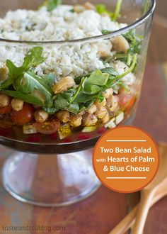 This Two Bean Salad with Hearts of Palm and Blue Cheese is a layered bean salad with beans, cucumbers, tomatoes, chickpeas, arugula, hearts of palm, blue cheese and a delicious vinaigrette. Make it for a refreshing and better-for-you lunch!