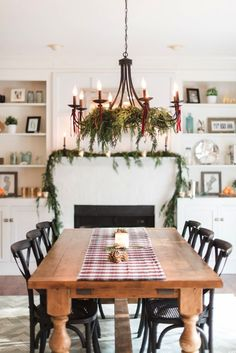 Cypress garlands on mantel and chandelier.  Fireplace and bookshelves in dining room