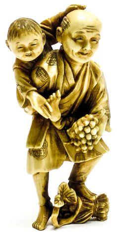 """De probable manufactura japonesa. """"Anciano con uvas y niño"""" realizado en marfil tallado con decoración a plumilla.  Altura: 8 cm."""