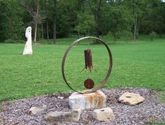 """George Weaver massive 'music' maker.  He says, """"Wind chime made from a steel pipe and a wood clacker.."""" Flea Market Gardening"""