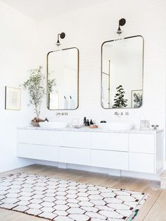 White bathroom with two mirrors and sinks
