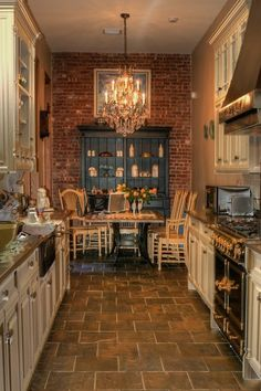Exposed brick kitchen- LOVE!! Love the cabinet, the chandelier, the table- everything!!