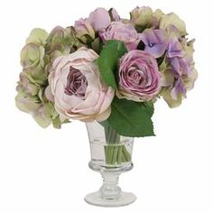 """Featuring faux cabbage roses and hydrangeas in a glass pedestal vase, this lovely arrangement brings a touch of natural style to your decor.    Product: Faux floral arrangementConstruction Material: Silk and glassColor: Pink, purple and greenFeatures: Includes roses, faux hydrangeas and cabbage rosesDimensions: 11.5"""" H x 12"""" Diameter"""