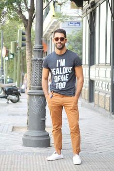 Shop this look on Lookastic:  http://lookastic.com/men/looks/charcoal-crew-neck-t-shirt-khaki-chinos-white-low-top-sneakers-brown-sunglasses/11359  — Charcoal Print Crew-neck T-shirt  — Brown Sunglasses  — Khaki Chinos  — White Canvas Low Top Sneakers