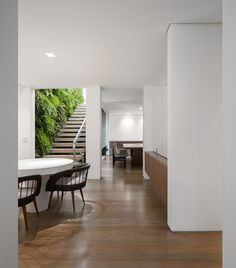 K House by Studio Arthur Casas - green wall entry stair, understated and modern dining and kitchen area