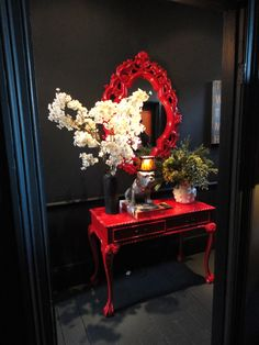 Abigail Aherne hallway. Love the red mirror and hall table!