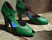 "EVA'- An exact copy of a late 40's/early 50's peep toe D'orsay pump that's open on the inside and has a rakish pointy ankle detail on the outer side. It's elegance with an ""edge"" and is our most popular new heel. Available in Pepper Green or Black kid leather. 3 ¼ inch heel, sizes 6 – 10. This style runs ½ size large. Order a ½ size smaller than you normally"