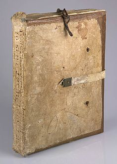 Medieval binding of whittawed leather over oak boards with a flat spine and two projecting flaps, at the top and bottom. Fastened to a staple at the bottom of the front cover are three links of a chain. A white strap, secured by a decorated metal plate to