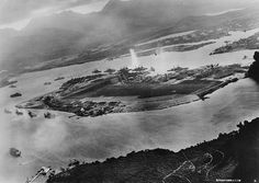 Photograph taken from a Japanese plane during the torpedo attack on ships moored on both sides of Ford Island shortly after the beginning of the Pearl Harbor attack. View looks about east with the supply depot submarine base and fuel tank farm in the right center distance. A torpedo has just hit USS West Virginia on the far side of Ford Island (center). Other battleships moored nearby are (from left): Nevada Arizona Tennessee (inboard of West Virginia) Oklahoma (torpedoed and listing)…