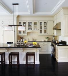 Exquisite dark wood flooring and dark countertop while everything else is creamy white