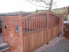 Garden Decor Artistic Driveway Decoration In Your Outdoor Home Areas With Brown Wood Wooden Driveway Gate And Brick Garden Fence Extraordinary Lift up Tight Privacy by Installing Wood Fence Designs Home design http://seekayem.com