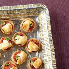 Tiny Tomato Tarts  Ingredients:   1/2 (14.1-oz.) package refrigerated piecrusts  1 (14.5-oz.) can petite diced tomatoes  1 tablespoon chopped fresh basil  2/3 cup mayonnaise  1/2 cup grated Parmesan cheese  1/4 cup (1 oz.) freshly shredded Cheddar cheese  1/4 cup (1 oz.) freshly shredded mozzarella cheese  Garnish: fresh basil leaves
