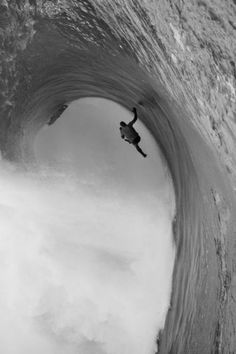 Cool black and white of surfer getting caught up in the wave...