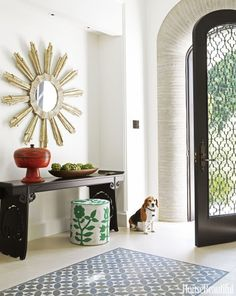 """A vintage mirror hangs over a custom console in the entry of a Los Angeles home designed by Betsy Burnham. Instead of runners, Burnham """"carpeted"""" the entry with inlaid mosaic stones by Country Floors. Click through for more foyer decorating ideas and designs."""