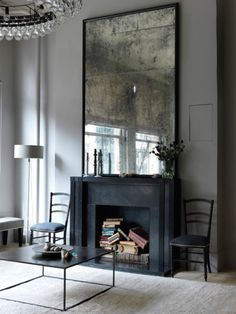 Oversized mirror creates an awesome focal point to this fab space. Accentuating the height of the ceilings. Love it!