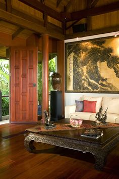 An Asian style living room with a tall stained wood ceiling and wood carved coffee table. A formal setting with unique wall art and red and purple accent pillows. Click to see how much it costs to hire an interior designer.