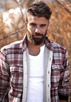 Rugged-looking bearded man in the wilderness.