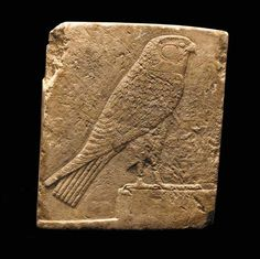 AN EGYPTIAN LIMESTONE SCULPTOR'S MODEL   Dynasty XXX to Ptolemaic Period, 380-30 B.C.   Decorated on one side in raised relief with a falcon on a rectangular base, facing right, its feathering rendered by careful incisions  4¾ in. (12 cm) high