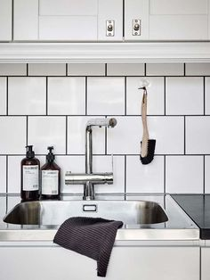 Stainless steel sink, irregular white tiles and black grout