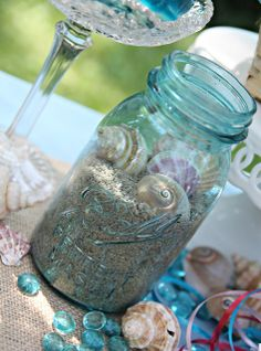 Mason jars filled with sand and shells: Mermaid Party Table Decor