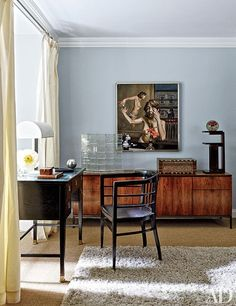 A corner of the bedroom showcases a Pieter Schoolwerth painting above a 1960s Knoll credenza; the Plexiglas sculpture is by Louise Nevelson, the circa-1900 desk and chair are both by Thonet, and the walls are painted in a Farrow & Ball blue.