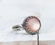 Sehr schöner, zarter und femininer Ring.  In die schöne Krönchen Ringfassung habe ich einen leicht schimmernden beigen Schmuckstein gesetzt.  Durch das silber der Fassung un der pastellfarbenen Schmuckstein...