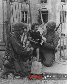 Private Roland Bonnell, left, Cleveland, Ohio, and Sergeant James Devine, right, New York City, New York, both members of an engineer unit now fighting in France, take time out to comfort a little French girl as U.S. troops force ahead in France.  Colleville, France.  13 June 1944.