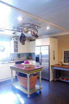 from karapaslaydesigns.blogspot.com, how cool is the revamped table as an island!? Also the reclaimed copper pipe pot rack?