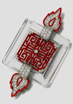 An Art Deco enamel, rock crystal and diamond brooch, Cartier, 1920s. Set at the…