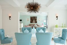 Love the tranquil colors in this dining room/living room shot...The upholstered tufted back aqua dining chairs and aqua wall color in the living room really marry the two rooms together.