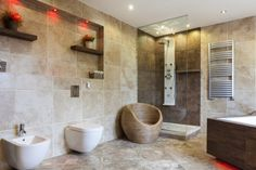 Luxury bathroom with large beige tiles with a glassed shower