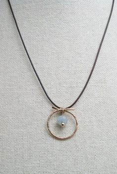 Gorgeous Aquamarine gemstone stands alone inside this hand forged 14K gold filled circle. The pendant is strung on waxed brown (vegan) cord and closes with hand made 14k gold filled hook and jumpring.