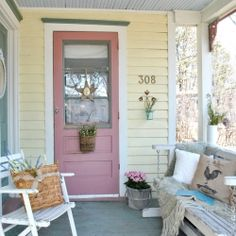 Farmhouse front porch wears combination of country colors selected to accent the trim of this Victorian cottage.