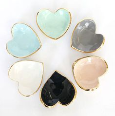 Heart shaped ring dish with a slight curve. Glazed in either white, blush, midnight, light blue, dark gray, mint or red with 22k gold luster overglaze on the edges. Size: 4X4X1 Made of high fire ceramic stoneware and glazed with high fire glaze, then a low fire gold luster overglaze in 22K. I recommend hand washing as gold is a soft precious metal and harsh dishwashing soaps can scratch it over time. Not food safe.