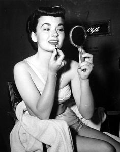 Ann Blyth adds a touch of lipstick between scenes of Katie Did It.