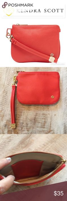 NWOT Kendra Scott Faux Leather Wristlet/Small/Red Travel in style with this Kendra Scott red Wristlet!  Perfect for your jewelry, faux leather, detachable strap, interior lining with one slit pocket, top zip closure.  Dimensions are L: 7 in, H: 5.25 in, W: .75 in, drop handle: 5.5 in.  Gold Kendra logo hardware still has clear plastic over it!  NWOT no trades/lowballs Kendra Scott Bags Travel Bags