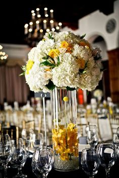 Yellow and white floral wedding centrepiece.    We love this as an idea for the Bride & Groom's centrepiece - bigger and bolder than other tables. Guest tables could have smaller low versions of this (if you choose not to use ceremony pomanders as centrepieces)