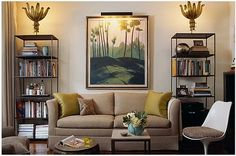 In a New York apartment, the space is well utilized with etageres framing a sofa. Sculptural uplights and a framed painting bring color and unique forms into the mix.