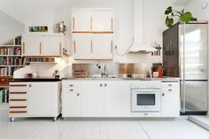 Kitchen in small flat. Cabinet on wheels. White floorboards.